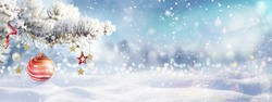 Beautiful winter Christmas scene nature panorama with snowdrifts and holiday lights. Snow-covered spruce branch and red ball on background of blue evening sky, falling flakes snow.