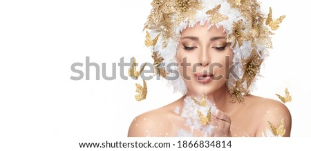 Beautiful winter fairy concept for Christmas with a young woman with gold and white festive hairstyle surrounded by golden butterflies blowing dainty white feathers from her hand with copy space Stockfoto ©