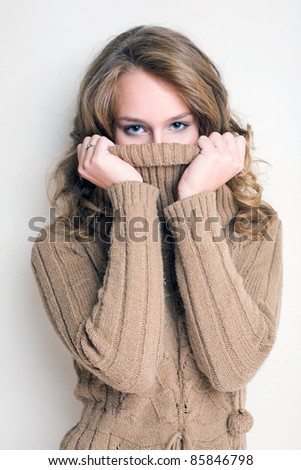Beautiful winter fashion girl playing with her turtleneck sweater.
