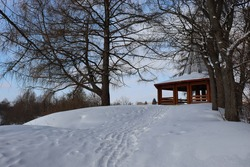 Beautiful winter landscape. A snowy path on the hillside, a wooden gazebo on the top. Snowdrifts, trees with a spreading crown. The ground is covered with snow. Blue sky and clouds. Picturesque nature
