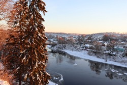 Beautiful winter landscape at sunset. A calm river, the reflection of the trees on the water. Tall green spruce, branches covered with snow. А colorful forest. Snowy riverbank. The picturesque nature.