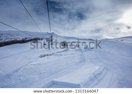 Beautiful winter landscape in the mountains of Georgia in the ski resort of Bakuriani. Mountains in the snow against the blue sky, gray clouds and ski lifts. Sunny day in the Caucasus #1313166047