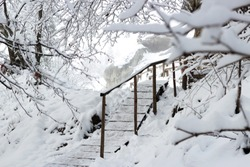 Beautiful winter landscape of Carpathians with spruce forest and wooden stairs covered with snow, horizontal winter outdoor, no people, selective focus