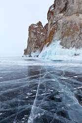 Beautiful winter landscape of frozen Lake Baikal on cold February day. Blue transparent ice with cracks near Rocks of Olkhon Island. A group of tourists take pictures of the icy rocks. Winter travel