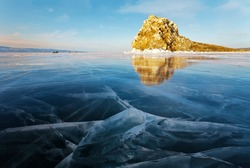Beautiful winter landscape of frozen Lake Baikal with clear blue ice with cracks near Edor rocky island on Olkhon. In the distance group of tourists and fishermen in cars. Winter holidays, ice travel