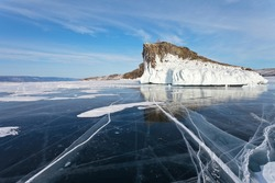 Beautiful winter landscape of frozen Lake Baikal with mirror-clear blue ice near the icy cliff Kobyliya Golova or Mare's Head is natural landmark of Olkhon Island.  Natural background. Ice travel