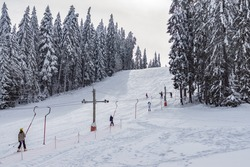 Beautiful winter landscape - skier sliding on ski lift up, pure white snow on the branches of evergreen trees. Perfect snowy weather conditions. Winter sports, skiing tourism, holidays in ski resorts.