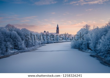 Beautiful winter landscape view of frozen Aurajoki river with Turku Cathedral and the old observatory building on Vartiovuori hill in the background in Turku, Finland - January 2018