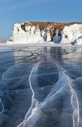 Beautiful winter landscape with blue transparent ice with cracks on a sunny frosty day. In the distance, icy white cliffs of Olkhon Island on frozen Baikal Lake. Unusual natural winter background