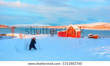 Beautiful winter landscape with old fishing red cabin (boathouse) boat at sunset - Photographer take a photo in snow - Landscape photographer taking picture photos with camera on fjord of Norway