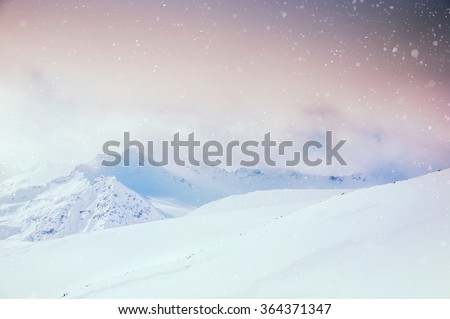 Stock Photo Beautiful winter landscape with snow-covered mountains at sunset.