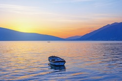 Beautiful winter Mediterranean landscape.  Sunset with fishing boat on the water. Montenegro, Adriatic Sea, Kotor Bay