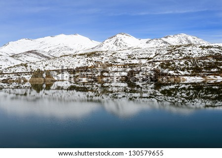 Beautiful winter mountains and lake reflection view on north of Palencia, Castilla y Leon, Spain. Natural park of Fuentes Carrionas and Fuente Cobre.