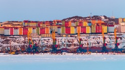 Beautiful winter panorama of the Arctic port town. View of the cranes and moorings of the seaport and colorful residential buildings on the high bank. Anadyr city, Chukotka, Siberia, Far East Russia.