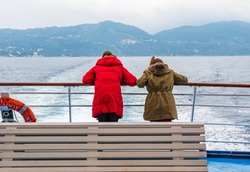 Beautiful winter scenery with adorable young girls enjoying ferry ride staring at the deep blue aegean sea. Children having fun on family vacation in Greece. Kids sailing on a boat.