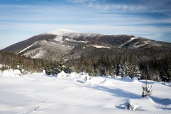 Beautiful winter scenery with Smrk mountain, plenty of snow, forest, hills and blue sky with few clouds on the way to Martinak in Beskydy mountains
