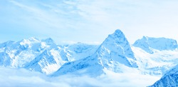 beautiful winter snow covered peaks of Caucasus mountain, Dombaj over clouds, Russia, panorama