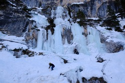 Beautiful winter view - frozen waterfall and silhouette of people by the lake Lago di Braies, Alta Pusteria, Dolomites, Italy