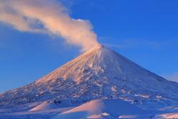 Beautiful winter volcanic landscape of Kamchatka Peninsula: view of eruption active Klyuchevskoy Volcano at sunrise. Eurasia, Russian Far East, Kamchatka Region, Klyuchevskaya Group of Volcanoes.