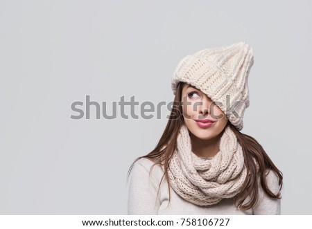 Shutterstock Beautiful winter woman looking up. Isolated on grey