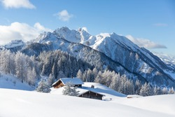 Beautiful winter wonderland mountain scenery with traditional mountain hut in the Alps