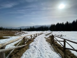 Beautiful wintery landscape overlooking the mountains. Wooden fence.