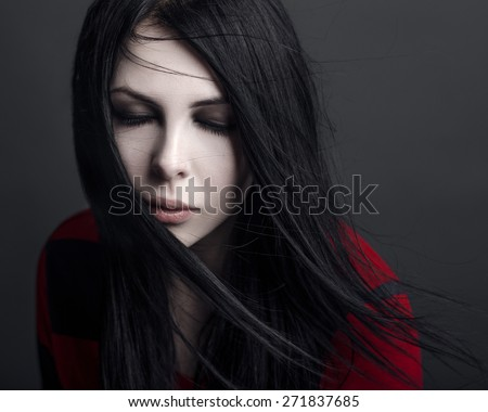 Beautiful witch and Halloween theme: portrait of a girl vampire with black hair
