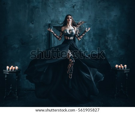 Beautiful witch floating in the air. Background dark room with a cold moonlight.. Girl dressed in a black dress with a long train. Creative color. #561905827