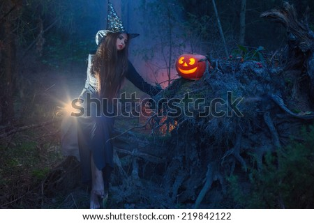 Beautiful witch with a pumpkin in the magic forest