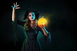 beautiful witch with hat conjures over jack-o-lantern pumpkin. Halloween party, witches ' Sabbath. Young beautiful brunette in witch costume, photo with art elements, magic smoke and grunge background