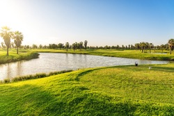 Beautiful, with green grass, golf course, with a pond, with sunny blue and clear sky. Portugal, Algarve.