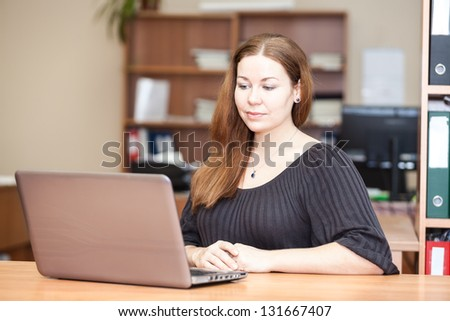 Beautiful woman a brunette working with laptop in office