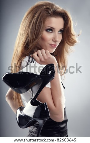 Beautiful woman after party holding shoes . Girl and shoe
