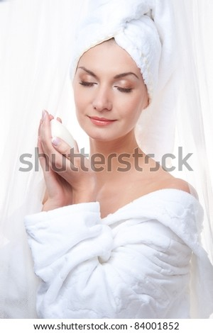 Beautiful woman after shower holding a soap - stock photo