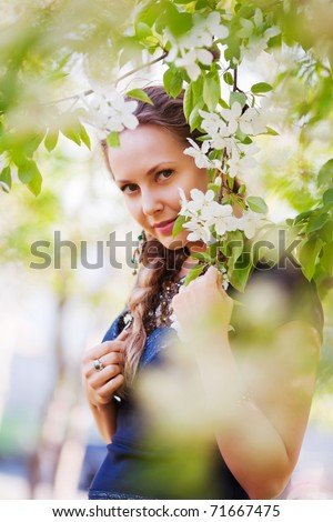 Beautiful woman among a spring blossom