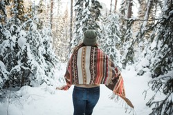 Beautiful woman among snowy trees in winter forest and enjoying  snow. Wearing plaid scarf and parka. Hipster boho style
