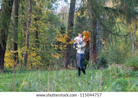 Beautiful woman and a baby girl walking in a forest among yellow trees