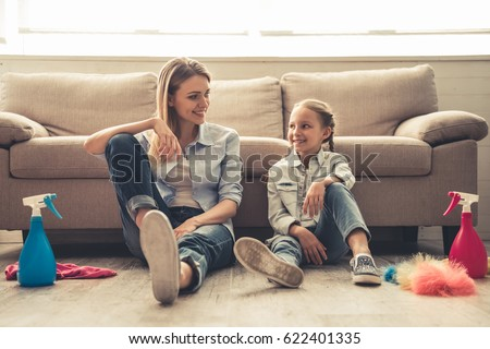Beautiful woman and her cute little daughter are sitting on the floor, looking at each other and smiling after cleaning their house ストックフォト ©