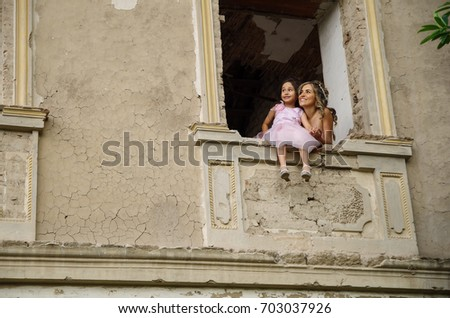 Beautiful woman and her cute little daughter smiling, wearing a pink princess dress, posing in a window castle while the little girl is sitting in the window