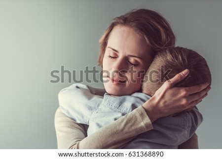 Beautiful woman and her cute little son are playing and smiling, on gray background. Boy is looking at camera Foto stock ©