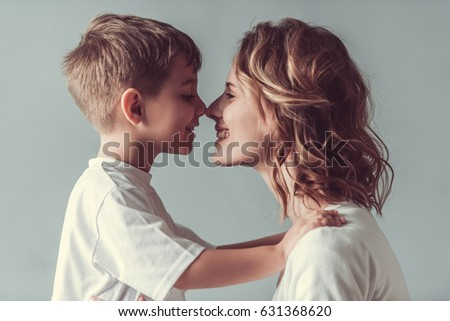 Beautiful woman and her cute little son are touching their noses and smiling, on gray background