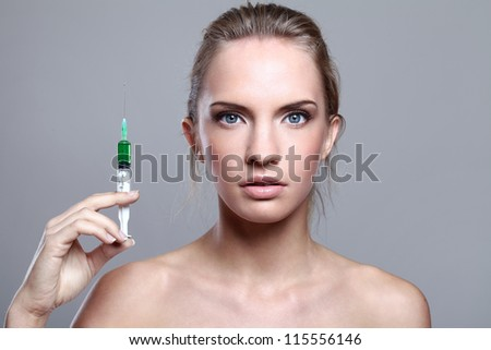 Beautiful woman and syringe with green liquid over gray background