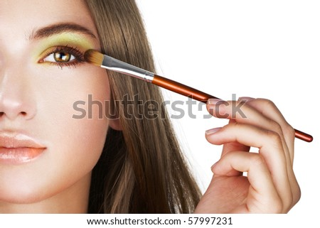Beautiful woman applying colorful eye makeup - stock photo