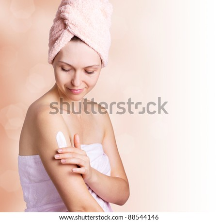 beautiful woman applying cream after bath