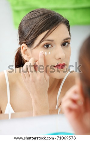 Beautiful woman applying cream on face at bathroom