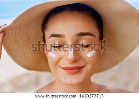 Beautiful woman applying cream sunscreen on tanned face. Sunscreen. Skin and body care. The girl uses a sunscreen for her skin. Portrait of a female holding suntan lotion and moisturizing sunscreen. #1420273715