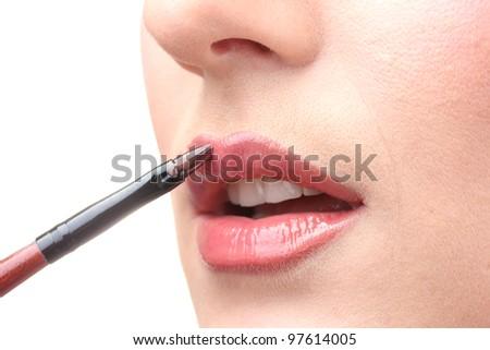 beautiful woman applying lip gloss