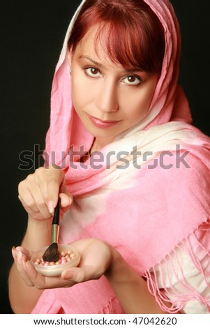 Beautiful woman applying make up. Powder and brush for makeup. Black background. - stock photo