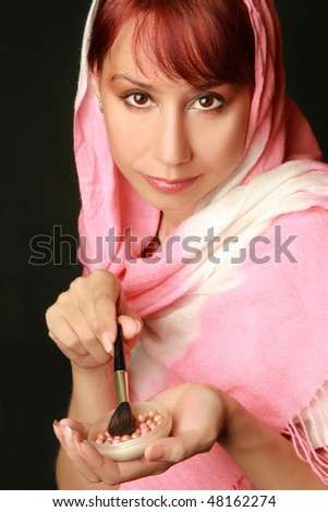 Beautiful woman applying make up. Powder and brush for makeup. Black background.