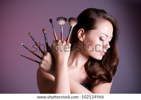 Beautiful woman applying makeup on face on dark background